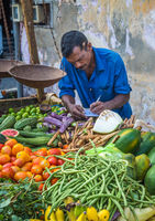 GALLE, SRI LANKA - February, 14, 2016: Street vendor with vegetables and vintage scales