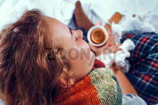 View from above on sick woman in bed holding a cup of tea with orange in it