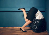 Woman with her head in garbage bin.