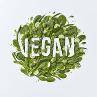 Round composition of different green vegetables with vegan paper lettering on a gray background with copy space. Healthy food concept. Flat lay