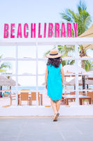 Young asian woman  at outdoor beach library next to bookshelf