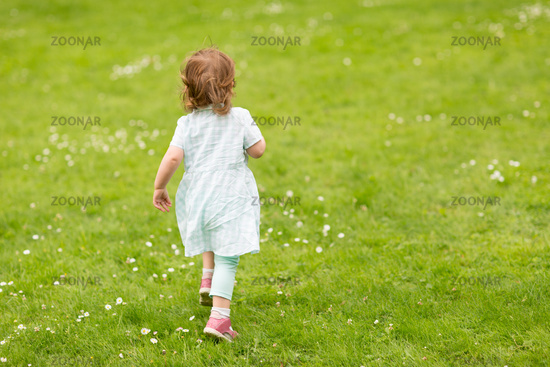 happy little baby girl running at park in summer