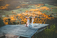 Woman watching the sunset over the mountain valley