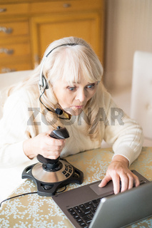 Senior woman plays video games with joystick on a laptop