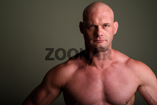 Bald muscular man shirtless against colored background