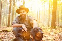 Jäger oder Förster im Wald mit Jagdhund