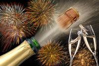 Champagnerflasche mit poppendem Korken und Sektgläser beim Anstossen vor Brillantfeuerwerk zu Neujahr 2019