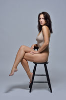 Beautiful woman in underwear sitting on the chair.