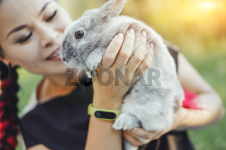 Close-up of Pretty Asian Hugging Bunny on Nature