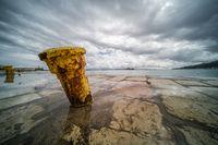 Steel anchoring bollard on the shore
