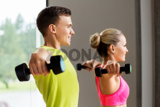 couple with dumbbells exercising in gym