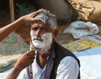 Shaving men on the street in India