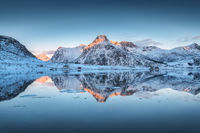 Fjord with reflection in water, snowy mountains at sunset