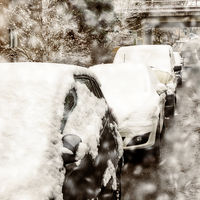 Parked cars in the street in winter