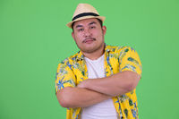 Young overweight Asian tourist man with arms crossed
