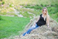 Nice lady posing sitting on the hay.