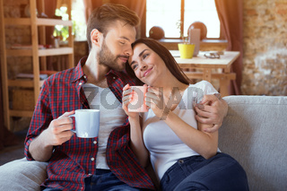 Happy couple sitting on couch.