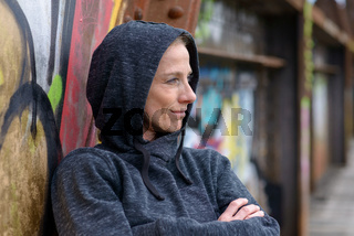 Woman in a hoodie leaning against graffiti