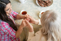 Elderly mother and her daughter holding hands while sitting at the table