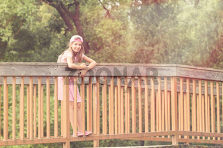 Cute girl standing on a bridge