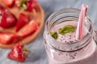 Closeup of organic milky strawberry smoothie with chia seeds and mint leaves in a glass with a straw on a wooden table. Healthy dessert. Top view