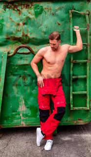 Porträt eines hemdlosen Mannes stehend an einem Container