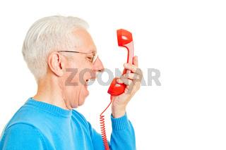Alter Mann brüllt wütend in rotes Telefon