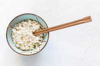 chopsticks in bowl with boiled rice on white
