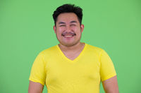 Face of happy young handsome overweight Asian man smiling