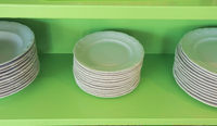 Set of white vintage plates on green shelf, antique tableware