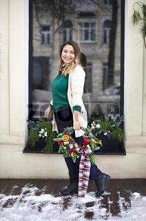Happy woman holding Christmas wreath