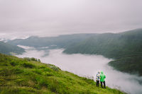 Hiking in Norway. Romantic couple of tourists on the edge of cliff looking on beautiful scenery. Back view of couple hugging at observation deck with panoramic view. Traveling together, adventure