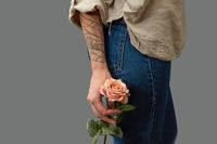 Hand of a woman with a tattoo holding a rose, slender legs of a girl in jeans on a dark background with space for text. Layout for postcard