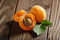 Ripe organic apricots on wooden table closeup