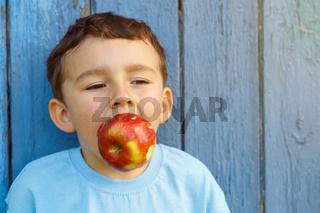 Apfel Frucht beißen Kind kleiner Junge Textfreiraum Copyspace draußen