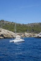 White camaran anchored near rocky coast
