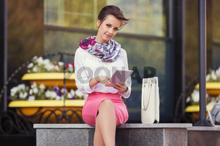 Young fashion business woman in white blouse using tablet computer at office building