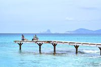People taking a photo in the wooden boardwalk, picturesque view to the turquoise water at the Formentera Island. Balearic Islands. Spain