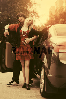 Happy young couple in love outside a new convertible car