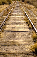Train tracks in the desert with dry vegetaion