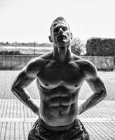 Handsome shirtless muscular man posing on glass