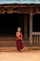 A young boy ties up his red buddhist monk robes out side his monastery.