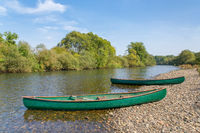 Two canoes lie on the bank of the river