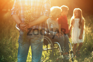 Man holds a bouquet behind his back. Woman in wheelchair with kids on the background