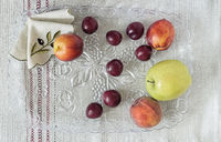 Plums, peaches, apples on a glass tray.