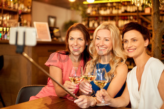 women taking picture by selfie stick at wine bar