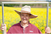 Farmer with photo frame is placed in canola field