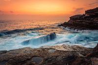 Stunning sunrise and waves crash over rocks on the Sydney sea coast