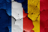 flags of France and Chad painted on cracked wall