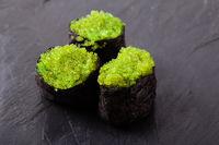 Tobiko green sushi set on the slate background